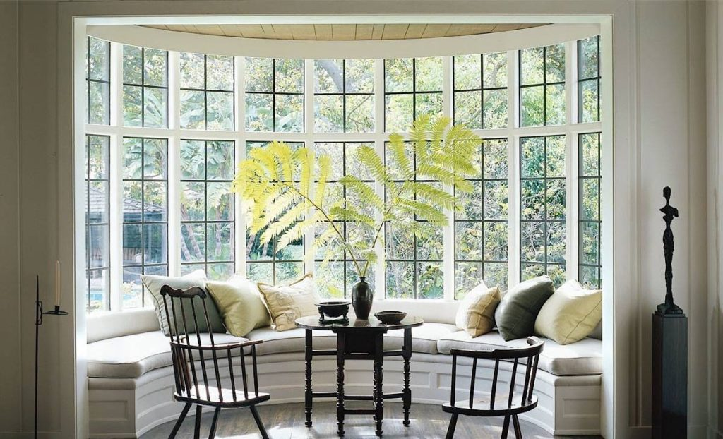 Large bay window with seating in front of it.
