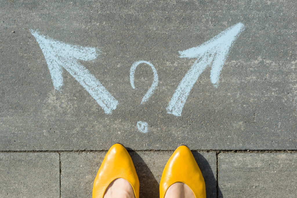 Female legs with 2 arrows and question mark, painted on the asphalt in indecision