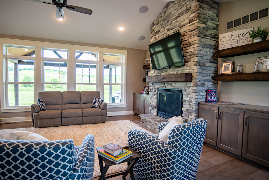 Living room with stone fireplace, and 4 large double-hung windows. A couch is placed in front of the windows.