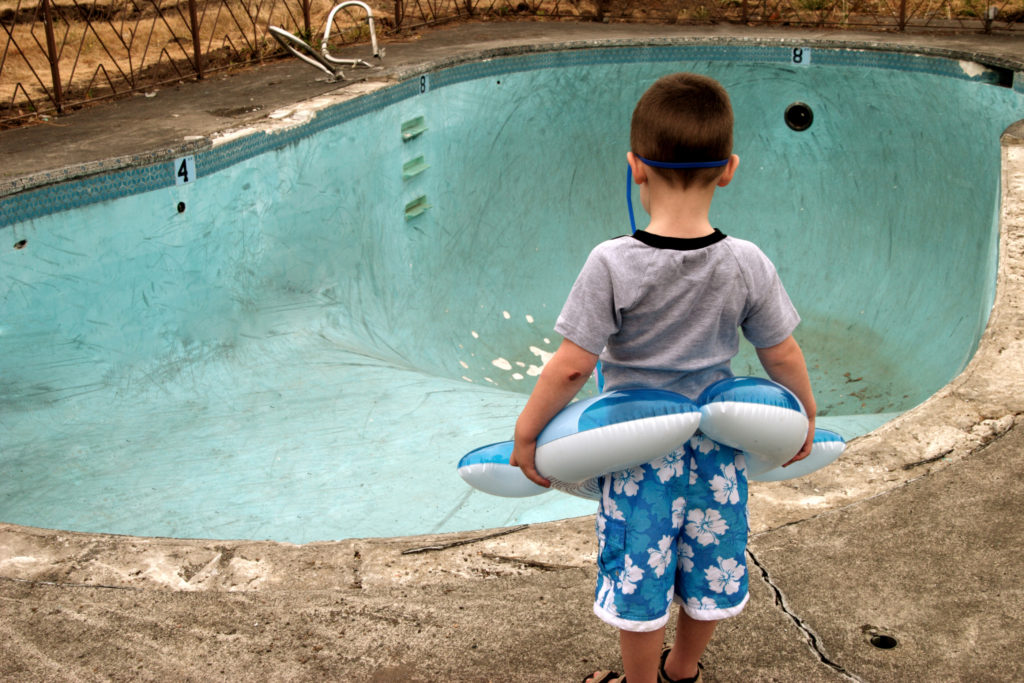 A young boy wearing a floaty disappointedly stares at an empty pool filled with air.