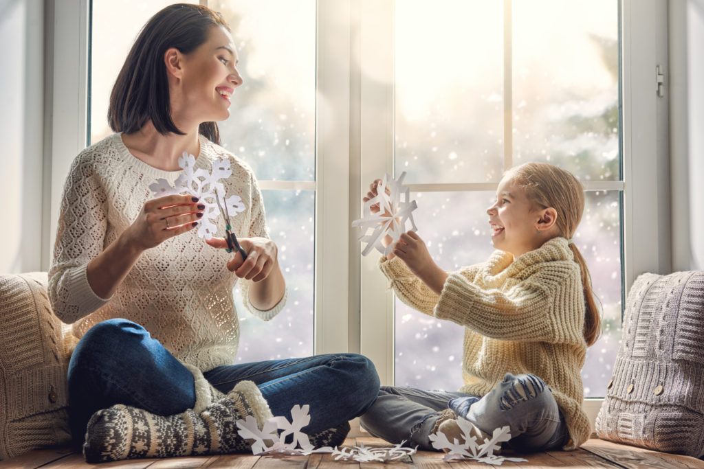 mother and daughter sit by a snowy window happily making paper snow flakes